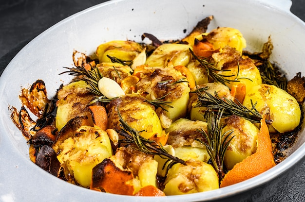 Aardappelen in de schil met kruiden en rozemarijn. zwarte achtergrond. bovenaanzicht