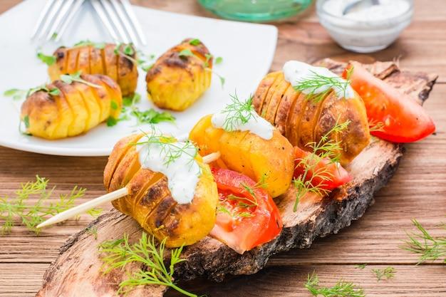 Aardappelen in de schil op vleespennen met zure room, tomaat en kruiden