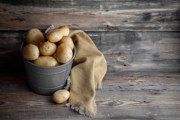 Aardappelen in een grijs emmer zijaanzicht op een donkere houten ruimte als achtergrond voor tekst