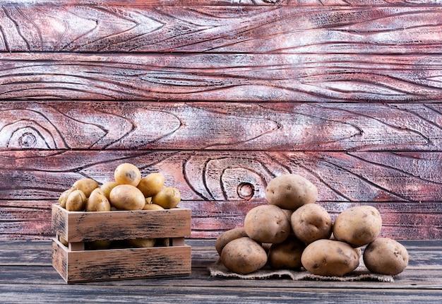 Aardappelen in een houten kist en op zak zijaanzicht op een houten tafel