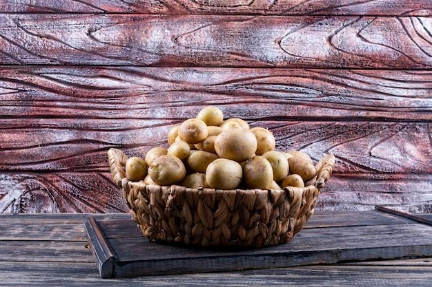 Aardappelen in een mand zijaanzicht op een houten tafel