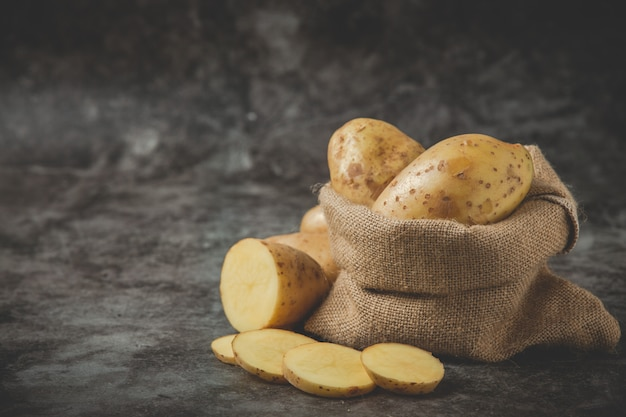 Aardappelen in plakjes rond de aardappelzak op grijze vloer