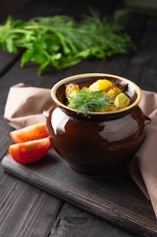 Aardappelen, kip en courgette gebakken in een aarden pot op een donkere achtergrond.