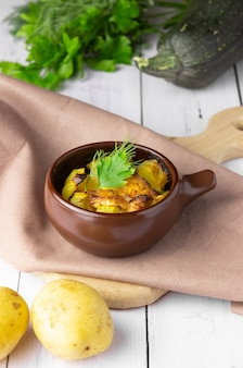 Aardappelen, kip en courgette gebakken in een aarden pot op een lichte achtergrond.