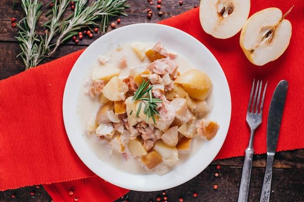 Aardappelen met spek en peer op tafel, restaurant schotel op een houten achtergrond bovenaanzicht