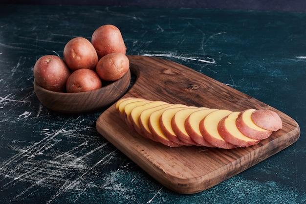 Aardappelen op een houten bord en in de beker.