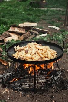 Aardappelen worden gebakken op de brandstapel. natuur in het dorp. het proces van het koken van voedsel. logt op de achtergrond in.