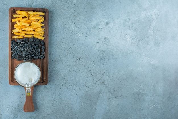 Aardappelfrietjes, zonnebloempitten en een glas bier op een bord, op de blauwe achtergrond.