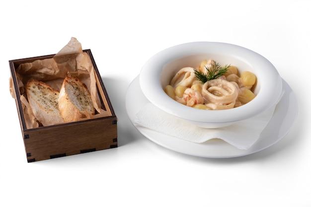 Aardappelgnocchi met zeevruchten, op een witte plaat, voor levering