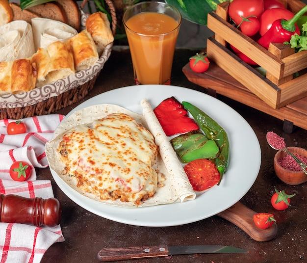 Aardappelgratin (gebakken aardappelen met room en kaas) met lavash en gegrilde rode groene paprika