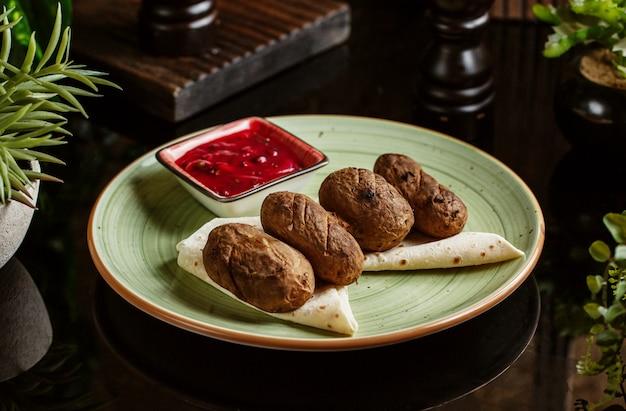 Aardappelkebab geserveerd op flatbreads met zure saus
