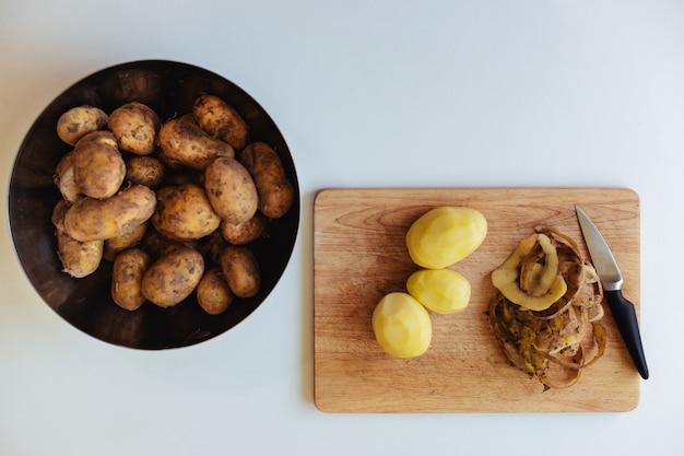 Aardappelmes en peeling op een houten plank op een witte keukentafel