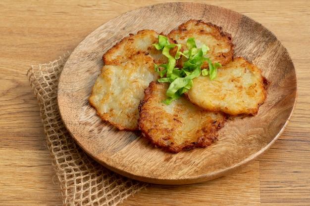 Aardappelpannekoeken op houten plaat
