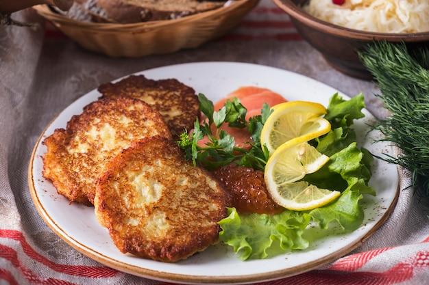 Aardappelpannenkoekjes c kaviaar en zalm. smakelijke aardappelpannenkoekjes op een plaat.