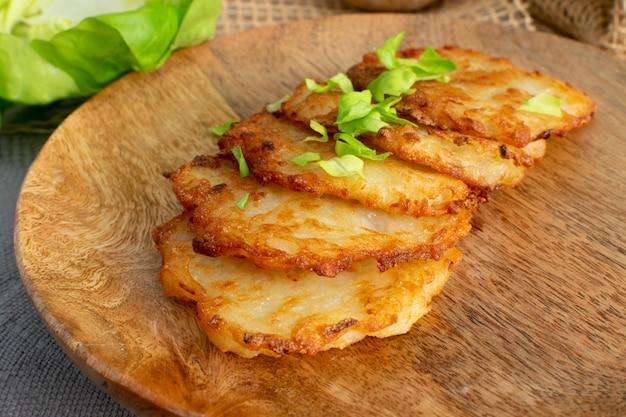 Aardappelpannenkoekjes, draniki, deruny, aardappel latkes, raggmunk of boxties op houten plaat.