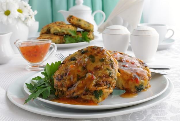 Aardappelpannenkoekjes met groenten, saus op het bord