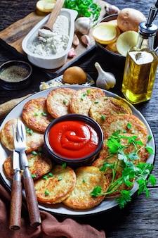 Aardappelpannenkoekjes met kwark met knoflook, peterselie, geserveerd met ketchup op een bord op een houten ondergrond, bovenaanzicht, close-up