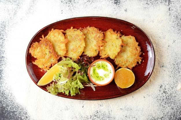 Aardappelpannenkoekjes met saus, citroen en sla