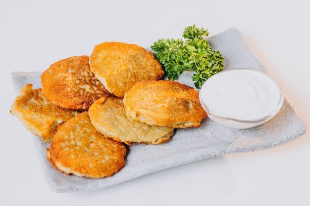 Aardappelpannenkoekjes met zure room geïsoleerd op wahite oppervlak