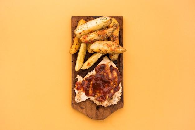 Aardappelpartjes en vlees met saus op een houten bord