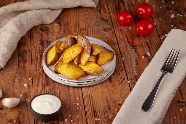 Aardappelpartjes, gebakken, houten achtergrond