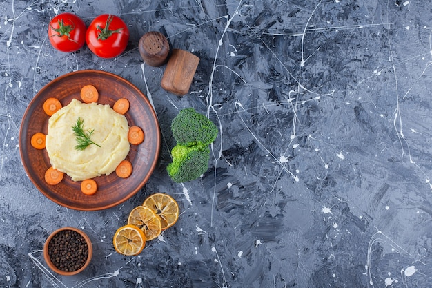 Aardappelpuree en gesneden wortelen op een bord naast groenten en kruidenkommen, op de blauwe tafel.