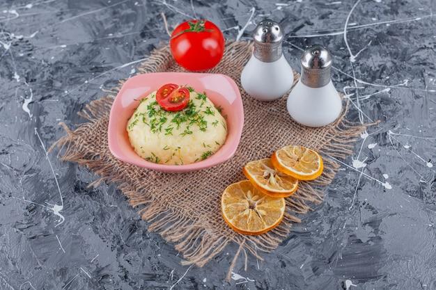 Aardappelpuree in een kom naast zout, citroen en tomaten op een jute, op de blauwe tafel.
