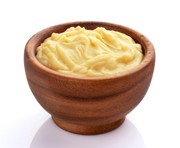 Aardappelpuree in houten kom die op witte achtergrond wordt geïsoleerd