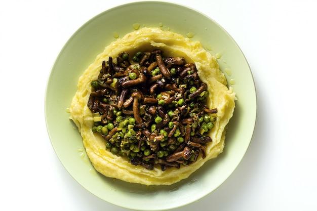 Aardappelpuree met champignons en doperwten op tafel. gezond lentevoedsel