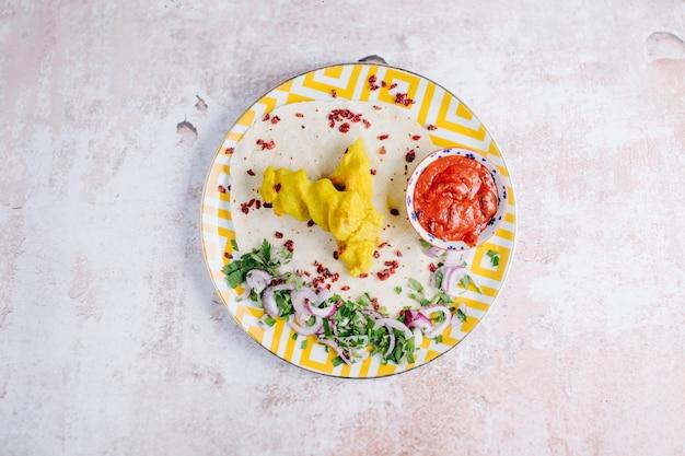 Aardappelpuree met tomatensaus, uien en kruiden in plaat.