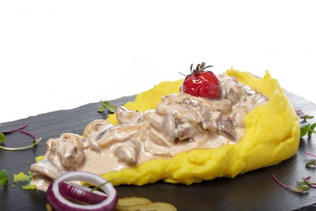 Aardappelpuree met vleessaus op witte achtergrond wordt geïsoleerd die