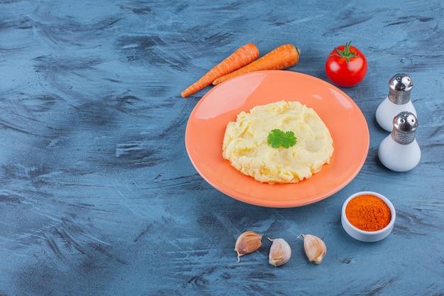 Aardappelpuree op een bord naast groenten en kruidenkommen, op de blauwe achtergrond.