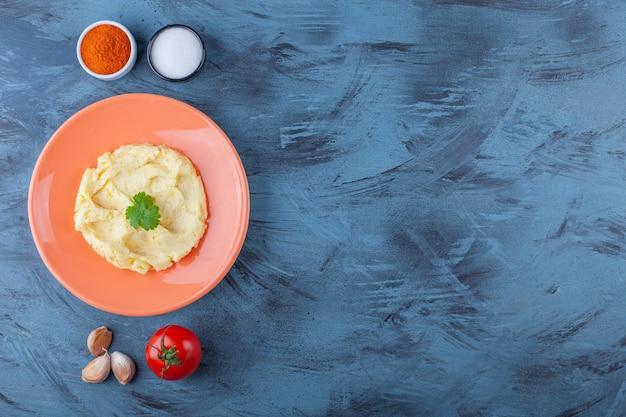 Aardappelpuree op een bord naast groenten en kruidenkommen op het blauwe oppervlak