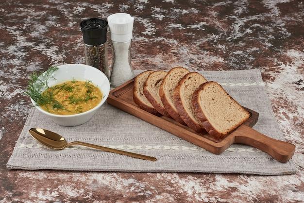 Aardappelpuree soep met kruiden in een witte kom