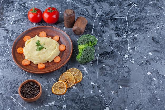 Aardappels puree en gesneden wortelen op een bord naast groenten en kruidenkommen, op de blauwe achtergrond.