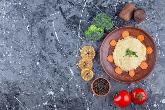 Aardappels pureren en gesneden wortelen op een bord naast groenten en kruidenkommen op het blauwe oppervlak