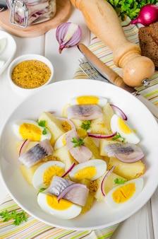 Aardappelsalade met gezouten vis, gekookte eieren, uien en peterseliebladeren.