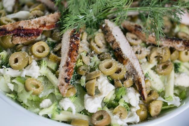 Aardappelsalade met groene olijven en gebakken kipfilet