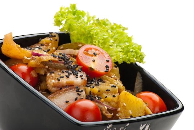 Aardappelsalade met spek, salade en uien op witte achtergrond
