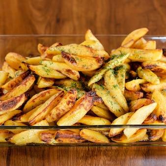 Aardappelschijfjes met kruiden in een transparante kom aardappels koken in dorpsstijl