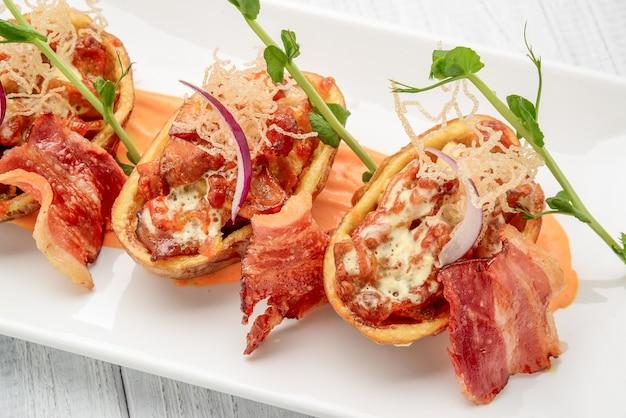 Aardappelschil met spek en kaas en tomatensaus op een houten tafel