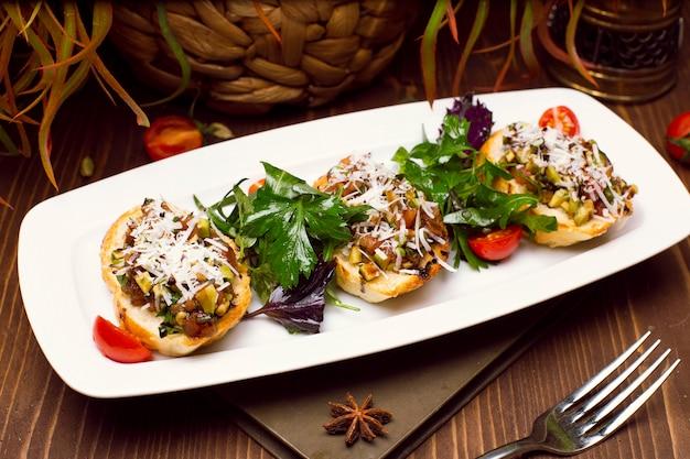 Aardappelschillen gevuld met champignons, ui, kruiden, groenten en gesmolten kaas