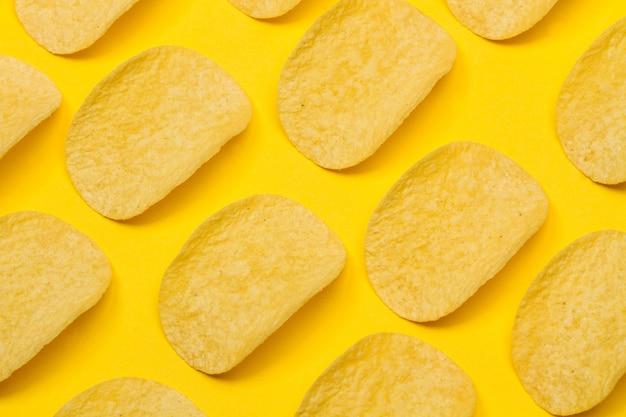 Aardappelschips in lijn op een gele achtergrond