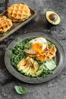 Aardappelwafel met gebakken ei, avocado en verse rucola