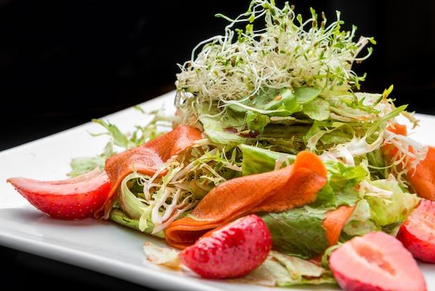 Aardbei, avocado, sla salade met cashewnoten op plaat