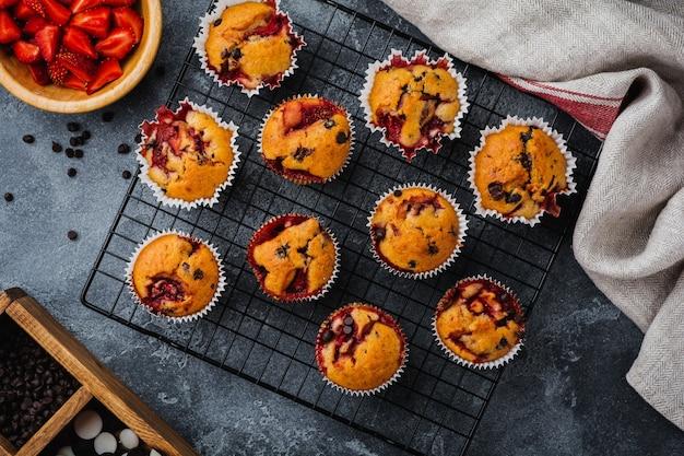 Aardbei chocolade cupcakes muffins op oude houten standaard op betonnen grijze ondergrond