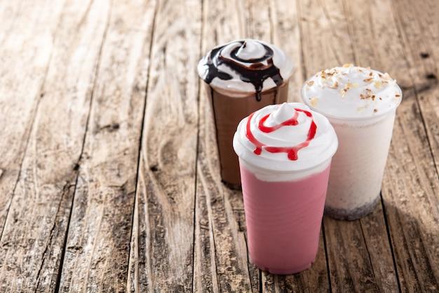 Aardbei, chocolade en witte iced milkshakes op houten tafel