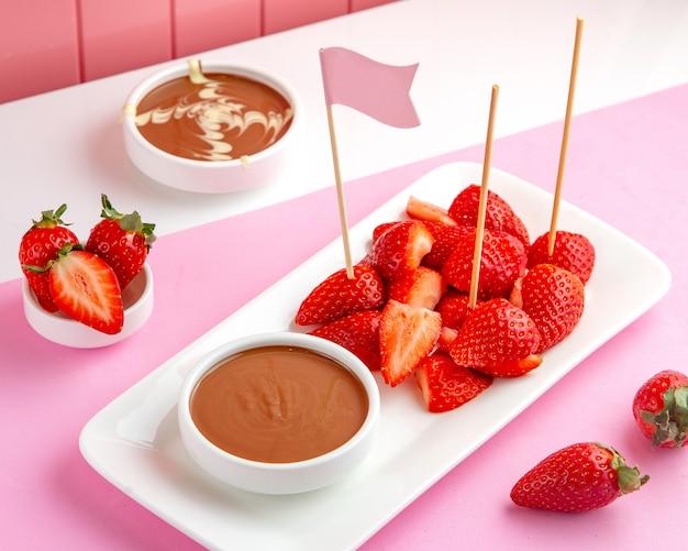 Aardbei chocolade fondue met gesmolten chocolade en aardbei op tafel