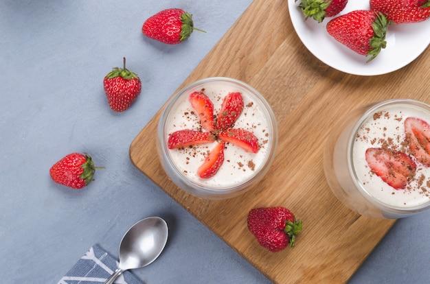 Aardbei dessert in een glazen pot met aardbeien op een grijze tafel
