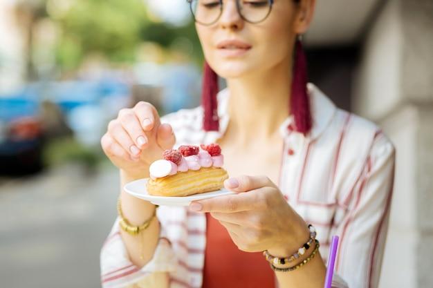 Aardbei dessert. rustige ontspannen jonge vrouw die bedachtzaam naar de smakelijke frambozen-eclair kijkt voordat hij deze eet